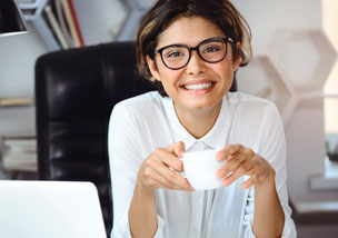 smiling woman at desk with cup of coffee